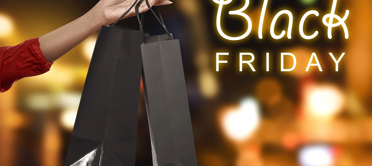 Hand holding black shopping bags in the mall. Black Friday Concepts