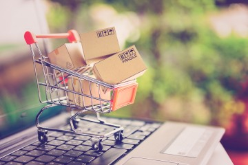 Online shopping and delivery service concept. Paper cartons in a shopping cart on a laptop keyboard, this image implies online shopping that customer order things from retailer sites via the internet.
