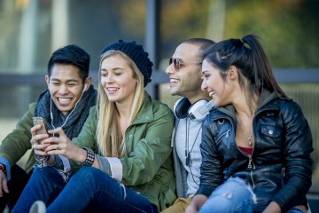 A multi-ethnic group of young adults are sitting in a public area outside. One woman is looking at her smartphone, and is getting ready to take a selfie of the group.