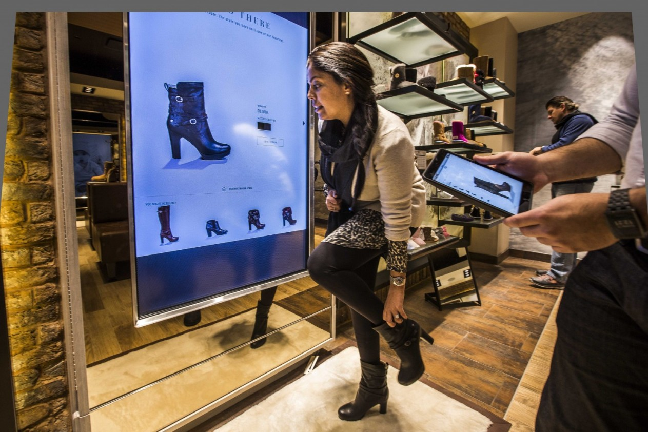 The new Ugg store at the Tysons Galleria serves as an innovation lab for the company. Here, a touchscreen uses RFID technology to identify the shoe Diana Krahn is wearing. (Jeffrey MacMillan/Capital Business)