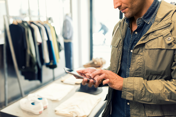 Male texting on smartphone in clothing store. Sms, message, mail